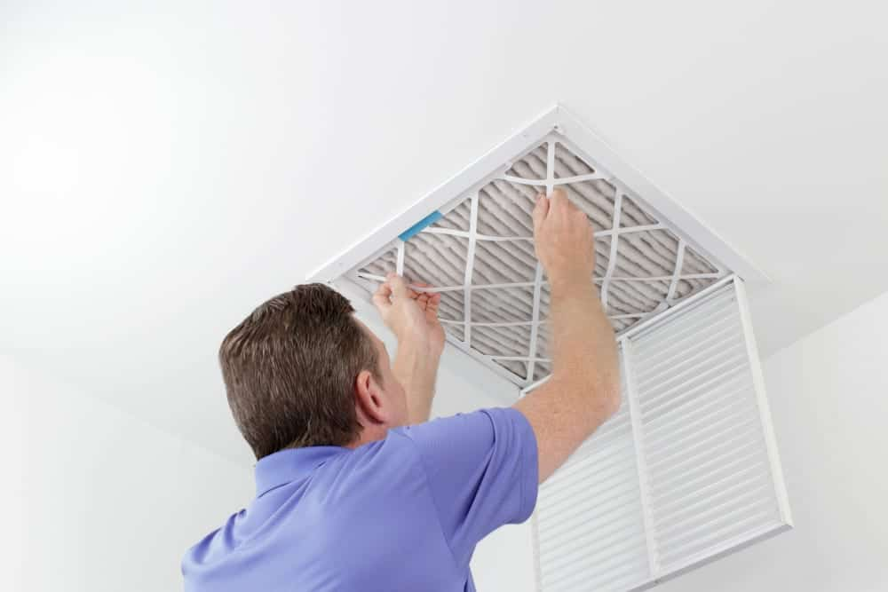 HVAC technician replacing a dirty air filter for air conditioner